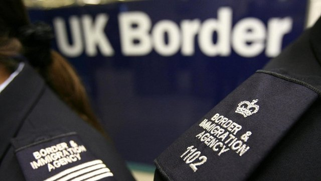 Border Agency officers standing in front of the UK Border sign
