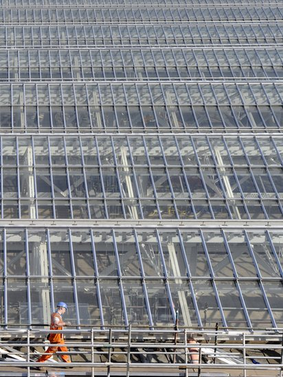 A worker walks along scaffolding on the new roof on Waverley railway station