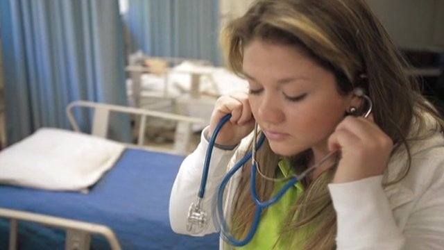 Woman listens with stethoscope