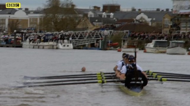 Swimmer's head bobbing in water ahead of Oxford crew