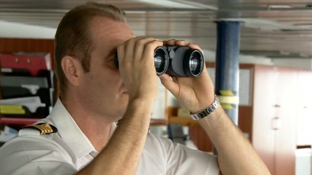 Crew of ship look through binoculars