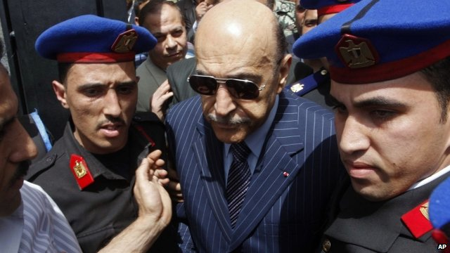 Omar Suleiman being escorted by police after submitting presidential candidacy papers