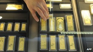 In a picture taken on March 2, 2011 a Chinese sales assistant arranges gold bars at a gold jewellery shop in Hefei, in east China's Anhui province.