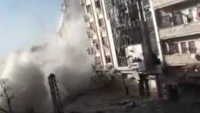 Military explosion on the front of a building in the Syrian city of Homs.