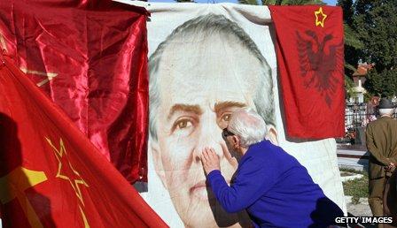 Albanian follower of Communist leader Enver Hoxha kisses his poster