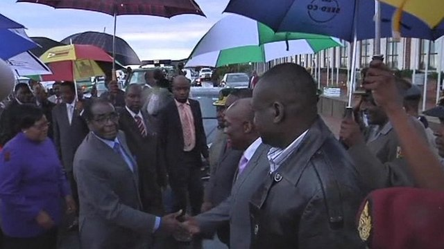 Robert Mugabe shaking hands with officials at Harare International Airport