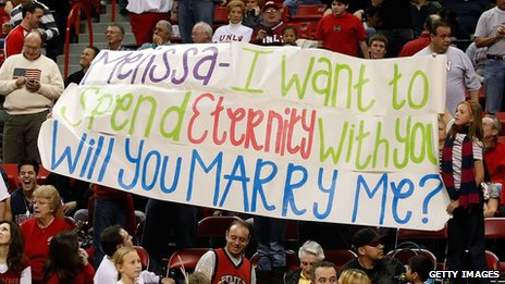 A fan holds up a banner bearing a wedding proposal at a basketball game between the Arizona Wildcats and the UNLV Rebels in 2008