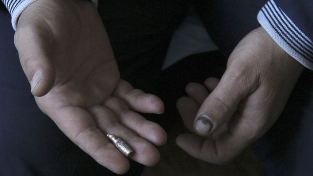 A hand holding a bullet