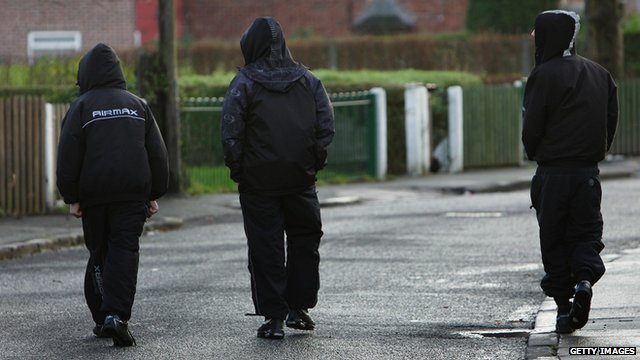 teenagers walking with their hoods up