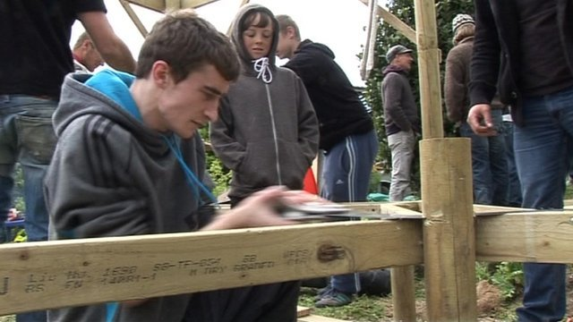 Young person sawing wood