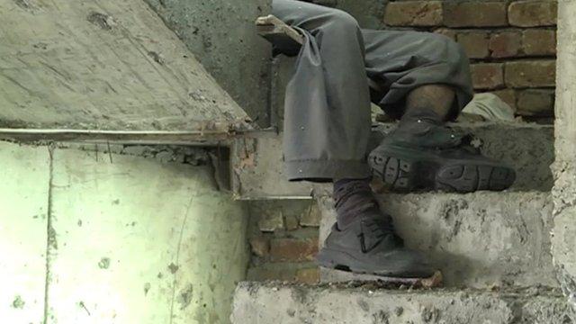 Militant's legs seen round corner of concrete staircase