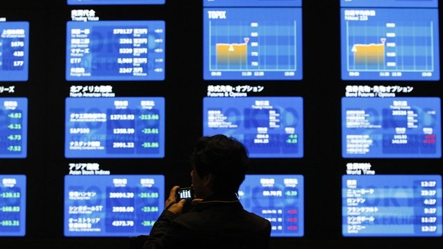 Man in front of Tokyo Stock Exchange displays showing market prices