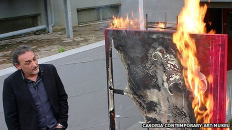 Antonio Manfredi torches a painting by French artist Severine Bourguignon in front of the Casoria Contemporary Art Museum