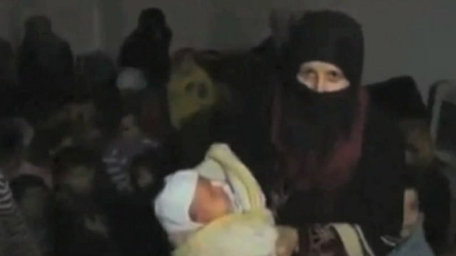 Woman in headscarf holding baby