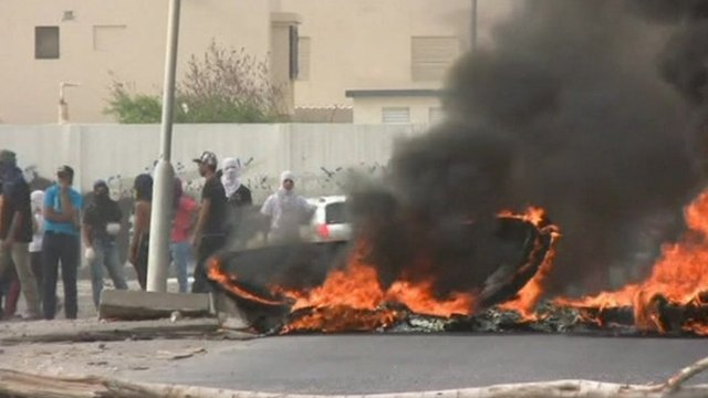 Protesters stand near fire in street in Bahrain