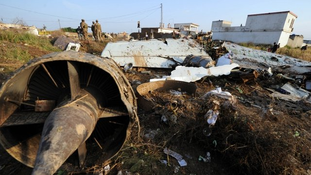 Pakistani soldiers stand next to the wreckage in Hussain Abad after a Bhoja Air Boeing 737 plane crashed on the outskirts of Islamabad
