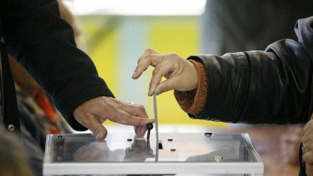 A woman casts her ballot at a polling station in the first round of the 2012 French presidential election