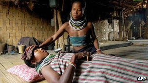 File photo of an Indian tribal woman attending to a malaria victim in the remote village of Bilaihum in the state of Tripur