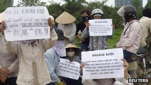 Farmers hold signs during a protest to protect their paddy fields from being part of a land grab to make way for the construction of a luxury Ecopark resort in Van Giang district, in Vietnam's northern Hung Yen province, outside Hanoi April 20, 2012