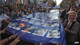 Members of the Madres de Plaza de Mayo hold, with hundreds of people, a large flag with the portraits of the disappeared during the last dictatorship (1976-1983), March 2012