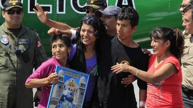 Injured police officer Luis Astuquillca stands next to his mother Fidela Vasquez (r) and other relatives as he arrives at Lima airport April 30, 2012