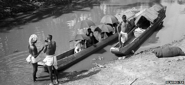 A group seated in two ferry canoes moored in a stream at an unknown location in India at least a century ago