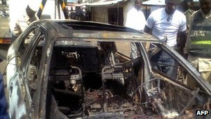 People gather around the car used to bomb This Day's office in Kaduna