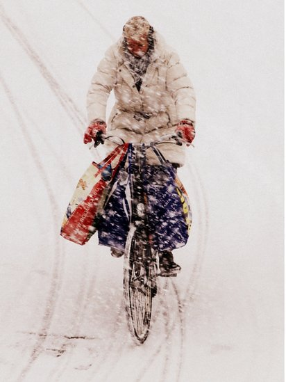 A person cycling through snow in the Netherlands