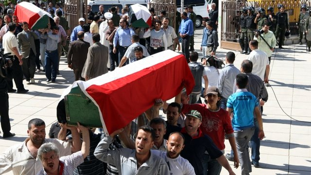 Syrians carry the coffins, covered in Syrian flags, of victims of the twin bombings that happened in Damascus on May 10