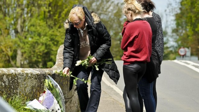 A woman places floral tributes on a bridge near where the bodies of a man and child were pulled from the River Avon
