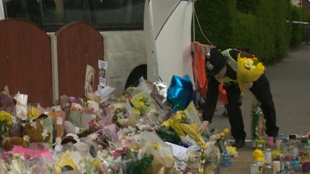 Flowers being laid outside the house by a police officer