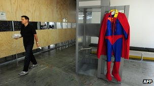 An employee walks past a Superman costume hanging on a phone booth door at the Facebook main campus in Menlo Park