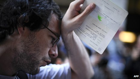 A man holds his savings book during a protest held outside Caja Madrid's headquarters