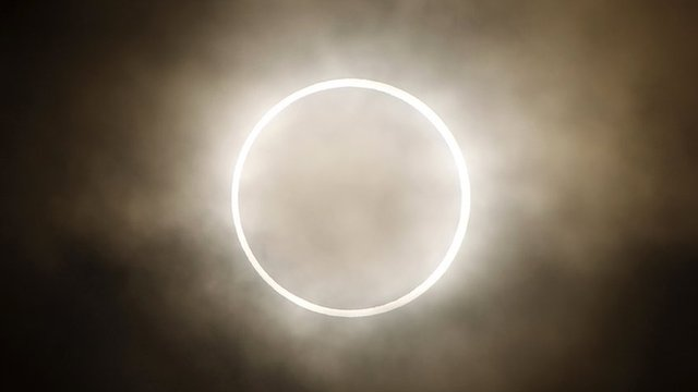 The moon slides across the sun, showing a blazing halo of light, during an annular eclipse at a waterfront park in Yokohama, near Tokyo.
