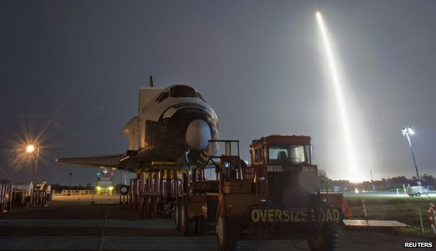 SpaceX launch behind a shuttle model
