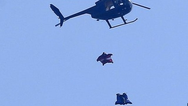 Wingsuit skydivers jump out of helicopter