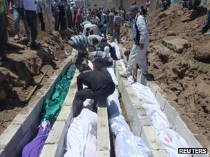 People gather to watch the burial of people reportedly killed by an army bombardment and raid by shabiha in the village of Taldou (26 May 2012)