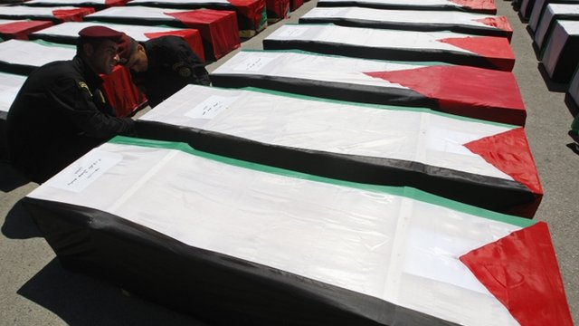 Palestinian security force adjust the flag covering a coffin