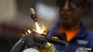A worker destroys a weapon confiscated by the police during a news conference in Caracas May 18 2012.