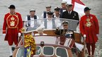 Queen Elizabeth and Prince Philip wave from a boat during a pageant in celebration