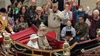 Queen Elizabeth II travels in a horse drawn carriage returning to Buckingham Palace