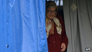 A woman leaves a tent set up as a temporary home