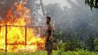 An ethnic Rakhine man holds homemade weapons as he stands in front of a house that was burnt during fighting between Buddhist Rakhine and Muslim Rohingya communities in Sittwe 10 June, 2012