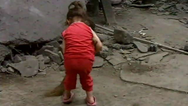 An Azeri girl is sweeping the factory floor they are living