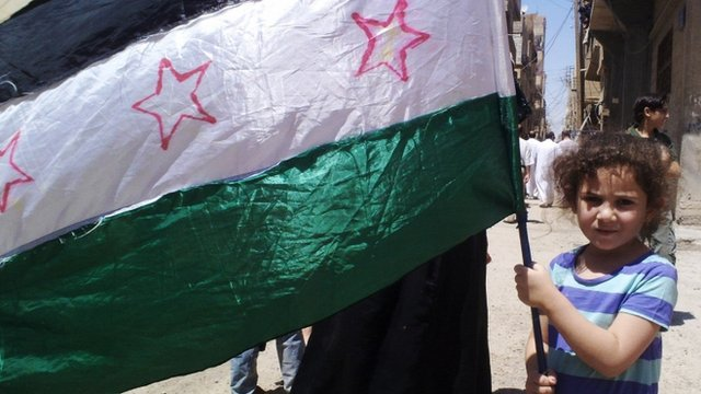 A girl holding the Syrian revolutionary flag