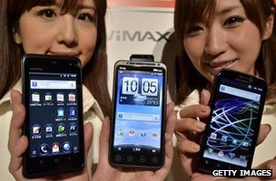 Models hold up Android-based smartphones
