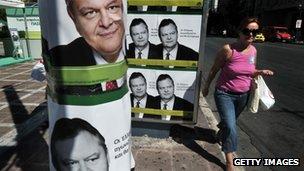 A woman walks by pre-election posters of Greek socialist party leader Evangelos Venizelos