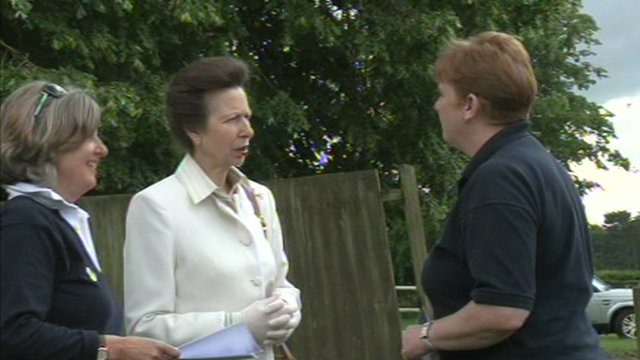 Princess Anne speaking to volunteers at the riding school