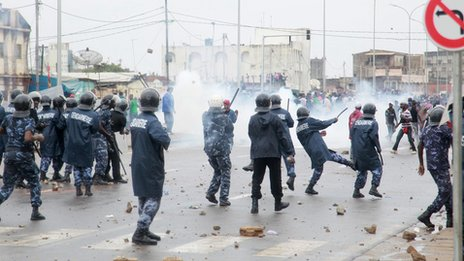Security forces fire tear gas as they clash with anti-government protesters in Lome