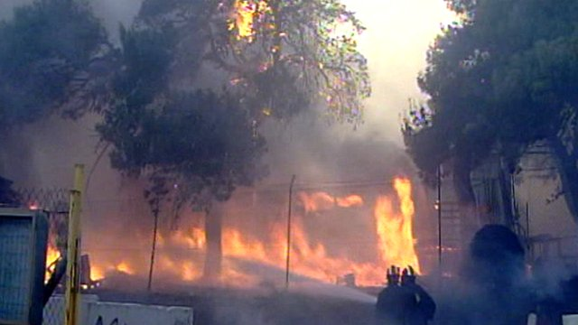 Fire crews try to put out wildfires in Greece